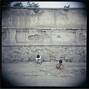 Children play in front of a wall with bullet holes in Kabul.