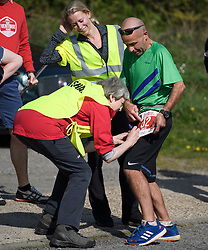 © Licensed to London News Pictures. 19/04/2019. Maidenhead, UK. Prime Minister THERESA MAY  signs a runners number as she helps out as a marshal at the Maidenhead Easter 10 run in her constituency of Maidenhead in Berkshire. Parliament currently on Easter recess after an extension to Article 50 was granted by the EU. Photo credit: Ben Cawthra/LNP