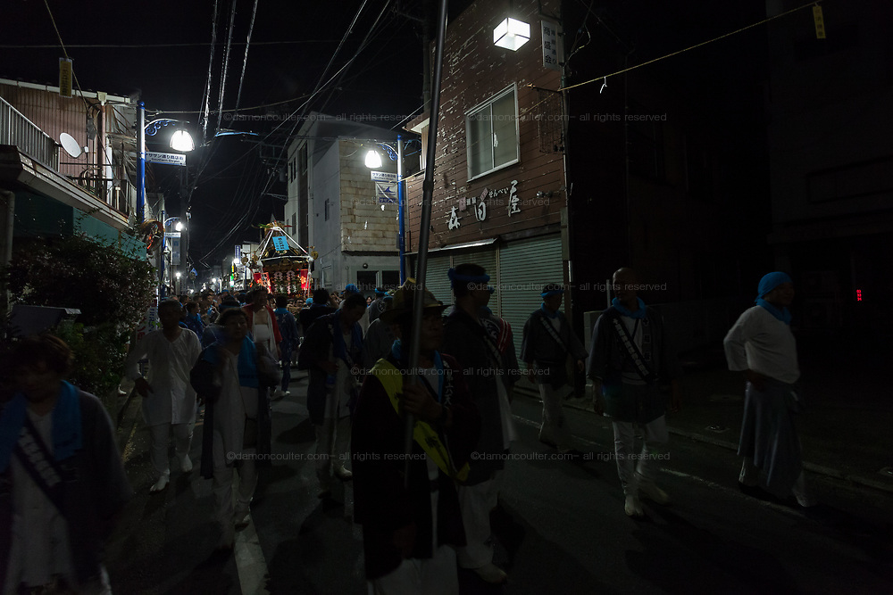 Mikoshi are carried through the streets at night during the Hamaorisai matsuri in Chigasaki, Kanagawa, Japan. Monday July 17th 2017. This festival is celebrated on Marine Day in Japan. Over 40 mikoshi (portable shrines) are paraded through the night to arrive on the coast at Southern Beach where they are blessed in a Shintoritual before being carried into the waves to be purified.