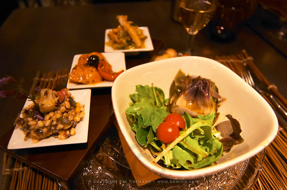 A salad with lettuce and tomato and an artichoke heart and three small side dishes in an oriental restaurant  Vienne, Isère Isere, France, Europe