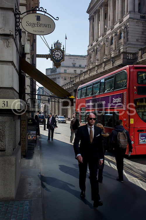 """Businessmen walk past the pillars of the Bank of England through high-intensity reflected light from a nearby plate glass on Threadneedle Street in the City of London<br /> Threadneedle Street is famous as the site of the Bank of England; the bank itself is sometimes known as 'the Old Lady of Threadneedle Street' and has been based at its current location since 1734. The etymology of the name Threadneedle Street is possibly from the Anglo-Saxon thread, meaning """"to prosper"""". Other theories, however, include that it originated as Three Needle Street (first attested in 1598), perhaps from a signboard portraying three needles, or from the three needles on the arms of needle-makers who had premises on the street. The threads and needles used by the members of the Worshipful Company of Merchant Taylors"""
