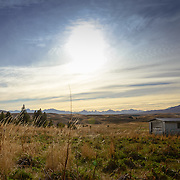 Farm shed in empty field with mountain range in background