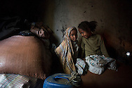 Yidenek, 4, and Tarikua, 8, sit on the sacks of teff flour that their mother, Abaynesh, was able to purchase by taking out a small loan from the micro-savings group she belongs to in Beben, Ethiopia. The family runs a small business selling injera and sauce to local patrons.   With her loan she was able to increase the amount of injera she sells from 20 a day to 100 by purchasing a large quantity of teff flour. She hopes to use her earnings to send her daughters to school. Sara A. Fajardo/Catholic Relief Services