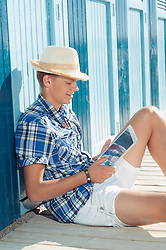 Teenager reading holiday beach summer straw hat