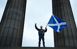 © Licensed to London News Pictures. 14/09/2014. Edinburgh, UK. A Yes campaigner waves the Saltire from the top of the Scottish National Monument in Calton Hill, Edinburgh. Photo credit: Isabel Infantes / LNP
