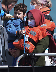 © Licensed to London News Pictures. 5/08/2021. Dover, UK. A  migrant carries a child onboard a Border Force vessel arriving at Dover Harbour in Kent after crossing the English Channel. Hundreds of migrants have made the crossing in recent weeks. Photo credit: Stuart Brock/LNP