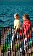 Women age 35 strolling around Lake Calhoun by brown fence.  Minneapolis  Minnesota USA