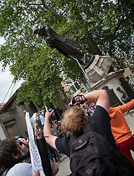 © Licensed to London News Pictures; 07/06/2020; Bristol, UK. People climb on the statue of slave trader Edward Colston before the statue is pulled down with a rope and thrown in Bristol Docks during a Black Lives Matter protest rally and march through the city centre in memory of George Floyd, a black man who was killed on May 25, 2020 in Minneapolis in the US by a white police officer kneeling on his neck for nearly 9 minutes. During the Bristol event the statue of Edward Colston was torn down and thrown into Bristol docks. Edward Colston (1636 – 1721) was a wealthy Bristol-born English merchant involved in the slave trade, a Member of Parliament and a philanthropist. He supported and endowed schools, almshouses, hospitals and churches in Bristol, London and elsewhere, and his name is commemorated in several Bristol landmarks, streets, three schools and the Colston bun. The killing of George Floyd has seen widespread protests in the US, the UK and other countries, despite the restrictions due to the Covid-19 coronavirus pandemic. People had been advised by the Bristol Mayor and Avon & Somerset's Chief Constable not to attend the event due due to the coronavirus pandemic and the need to maintain social distancing to avoid the spread of the virus. Photo credit: Mark Simmons/LNP.