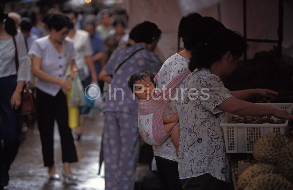 A child clings to the back of her mothers pouch while shopping at a street market in this highly-populated south-east Asian city, on 10th August 1994, in Macau, China. Macau is now administered by China as a Special Economic Region SER, home to a population of mainland 95% Chinese, primarily Cantonese, Fujianese as well as some Hakka, Shanghainese and overseas Chinese immigrants from Southeast Asia and elsewhere. The remainder are of Portuguese or mixed Chinese-Portuguese ancestry, the so-called Macanese, as well as several thousand Filipino and Thai nationals. The official languages are Portuguese and Chinese.