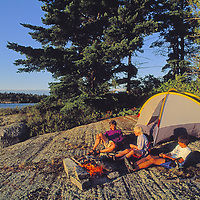A family camps on smooth, glaciated rock by lake.