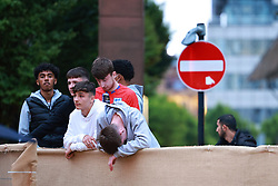 © Licensed to London News Pictures . 18/06/2021. Manchester, UK. Youngsters watch the match from over a fence outside Impossible Bar in Manchester City Centre . Football fans watch the European Cup tie between England and Scotland at Wembley Stadium via screens in pubs and venues around Manchester City Centre . Photo credit: Joel Goodman/LNP