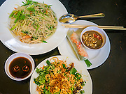 07 APRIL 2012 - HANOI, VIETNAM: Stir fried rice noodle vermicelli with shrimp and pork (top), fresh spring roll (right) and papaya salad with peanuts and dried beef in a restaurant in Hanoi, the capital of Vietnam. Hanoi is one of the oldest cities in Southeast Asia. It was established in 1010 A.D.   PHOTO BY JACK KURTZ