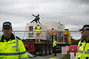 Anti-fracking  activists and protesters outside the gates of Quadrillas fracking site June 31st, Lancashire, United Kingdom. An activists got on the truck which kept moving and took hin inside the Quadrilla perimeter. The struggle against fracking in Lancashire has been going on for years. The fracking company Quadrilla is finally ready to bring in a drill tower to start drilling and anti-frackinhg activists are waiting in front of the gates to block the equipment getting in. Fracking is a destructive and potential dangerous and highly contentious method of extracting gas and this site will be the first of many in the United Kingdom reaching miles out under ground.