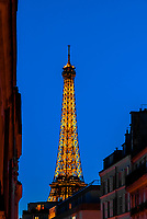 Twilight view of the Eiffel tower from Rue St. Dominique, Paris, France.  It is the world famous wrought-iron lattice tower that is the most famous landmark of Paris, France.