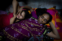 Sex worker Munnie, 15, left, is consoled by her grandmother Jova, 47, after work at brothel in Tangail, Bangladesh.