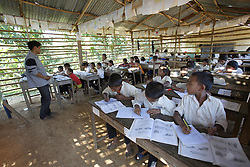 Unnamed children study in a (no grade given) class which is a bamboo structure outside the school building. At the primary school in Phangthong Village, Pha Oudom District, Bokeo Province, Lao PDR