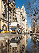 The Dakota and The San Remo buildings reflect in the street puddle in Manhattan, New York City.