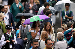 Spectators shelter under umbrellas as it rains on day eight of the Wimbledon Championships at The All England Lawn Tennis and Croquet Club, Wimbledon.