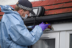 © Licensed to London News Pictures. 04/04/2018. London, UK. A member of a police search team attempts to recover a bullet from the window frame of a property on Chalgrove Road in Tottenham, north London where 17 year old Tanesha Melbourne was shot dead. A recent spree of killings in the capital has taken the murder toll for the year so far to 48. Photo credit: Ben Cawthra/LNP