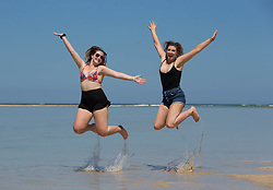 © Licensed to London News Pictures.  13/06/2021. Falmouth, UK. Rachel and Chelsea are having fun during the sunny day on Hayle Beach, Cornwall. Photo credit: Marcin Nowak/LNP
