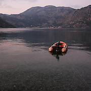 """A boat in Perast bay. There are several arguments about the derivation of the name  """"Montenegro"""", one of these relates to dark and deep forests  that once covered the Dinaric Alps, as it was possible to see them from the sea. <br /> Mostly mountainous with 672180 habitants on an area of 13812 Km², with a population density of  48 habitants/Km². <br /> It borders with Bosnia, Serbia, Croatia, Kosovo and Albania but  Montenegro has always been alien to the bloody political events that characterized Eastern Europe in recent decades. <br /> From 3 June 2006, breaking away from Serbia, Montenegro became an independent state. <br /> In the balance between economy devoted to sheep farming and a shy tourist, mostly coming from Bosnia and Herzegovina, Montenegro looks to Europe with a largely unspoiled natural beauty. <br /> Several cities in Montenegro, as well as the park Durmitor, considered World Heritage by UNESCO but not yet officially because Montenegro has yet to ratify the World Heritage Convention of UNESCO."""