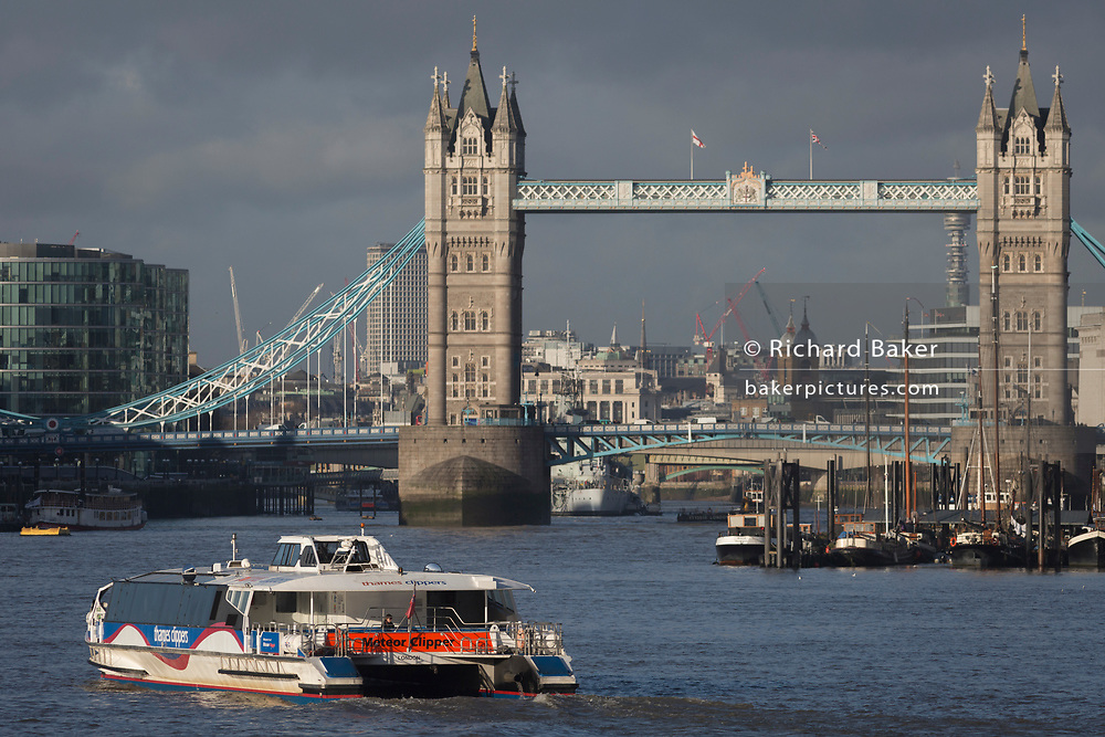A Thames Clipper passenger riverboat service heads upriver before continuing under Tower Bridge on the river Thames, on 17th January 2020, in London, England.
