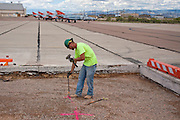 Laborer Jaysen Raymond hammers down a stake as construction crews at work building new runways at Holloman Air Force Base in Otero County. HAFB received over $21 million to upgrade various facilities as part of the Recovery and Reinvestment Act.