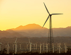 Turbines at wind farm in Palm Springs, California at sunset.
