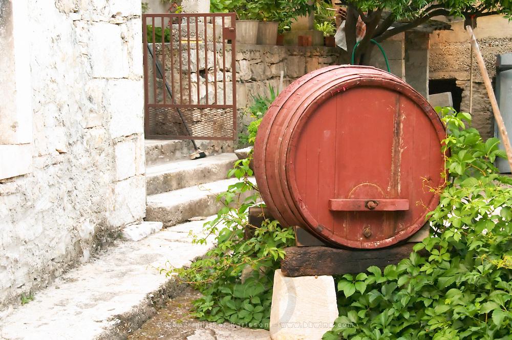 An old wooden barrel used for decoration in the garden. Toreta Vinarija Winery in Smokvica village on Korcula island. Vinarija Toreta Winery, Smokvica town. Peljesac peninsula. Dalmatian Coast, Croatia, Europe.