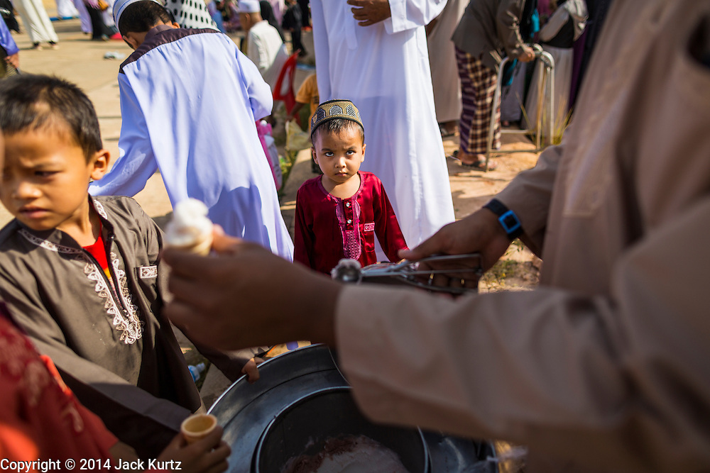 28 JULY 2014 - KHLONG HAE, SONGKHLA, THAILAND: A child waits for ice cream after Eid services at Songkhla Central Mosque in Songkhla province of Thailand. Eid al-Fitr is also called Feast of Breaking the Fast, the Sugar Feast, Bayram (Bajram), the Sweet Festival and the Lesser Eid, is an important Muslim holiday that marks the end of Ramadan, the Islamic holy month of fasting.   PHOTO BY JACK KURTZ