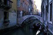 Peaceful shot of canal with beautiful architecture including an arched foot bridge and an empty gondola, Venice, Italy...Subject photograph(s) are copyright Edward McCain. All rights are reserved except those specifically granted by Edward McCain in writing prior to publication...McCain Photography.211 S 4th Avenue.Tucson, AZ 85701-2103.(520) 623-1998.mobile: (520) 990-0999.fax: (520) 623-1190.http://www.mccainphoto.com.edward@mccainphoto.com.