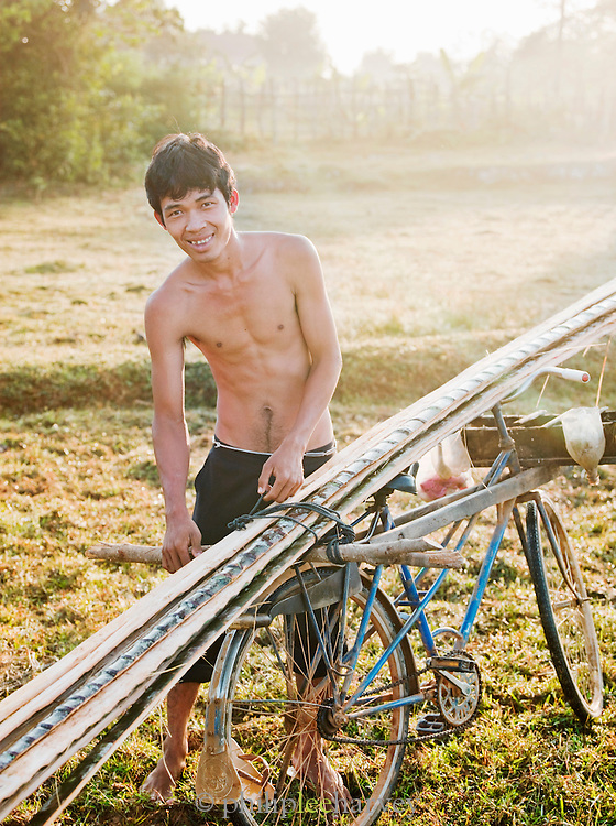 A young man attaches wooden poles to his bicycle in rural Cambodia
