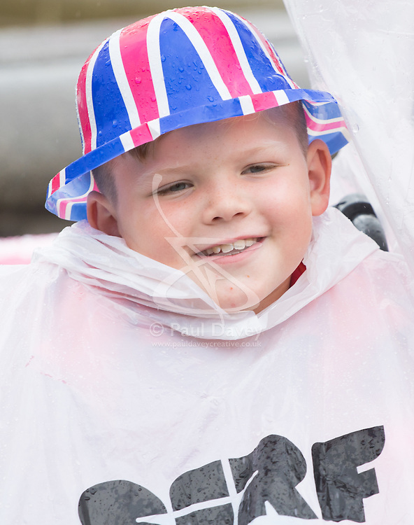 Trafalgar Square, London, June 12th 2016. Rain greets Londoners and visitors to the capital's Trafalgar Square as the Mayor hosts a Patron's Lunch in celebration of The Queen's 90th birthday. PICTURED: A little boy enjoys the atmosphere despite the rain.