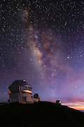 A brilliant Milky Way fills the evening sky above the Gemini Observatory, as a layer of thin, high, cirrus clouds blowing over the summit reflects the waning glow of the sunset.  This 15 second exposure captures a meteor streaking through the earth's atmosphere, adding another dramatic element to the visually stunning scene.<br /> <br /> Home to several of the world's most powerful telescopes, including the Gemini in the foreground, the summit of Mauna Kea is the premier star gazing site on the planet.