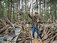 Adam Morales, folk artist in Pierre Part, Louisiana posing behind  the back of his musuem, Adam's Cypress Swamp Driftwood Family Museum.