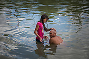 """Twelve year-old Honduran migrant Anyi shaves the head of her father Misael as they bathe in the Rio Grande near a makeshift encampment where they've stayed with fellow asylum seekers since being sent back to Mexico from the U.S. under the """"Remain in Mexico"""" program, officially named Migrant Protection Protocols (MPP), in Matamoros, Tamaulipas, Mexico, October 6, 2019."""