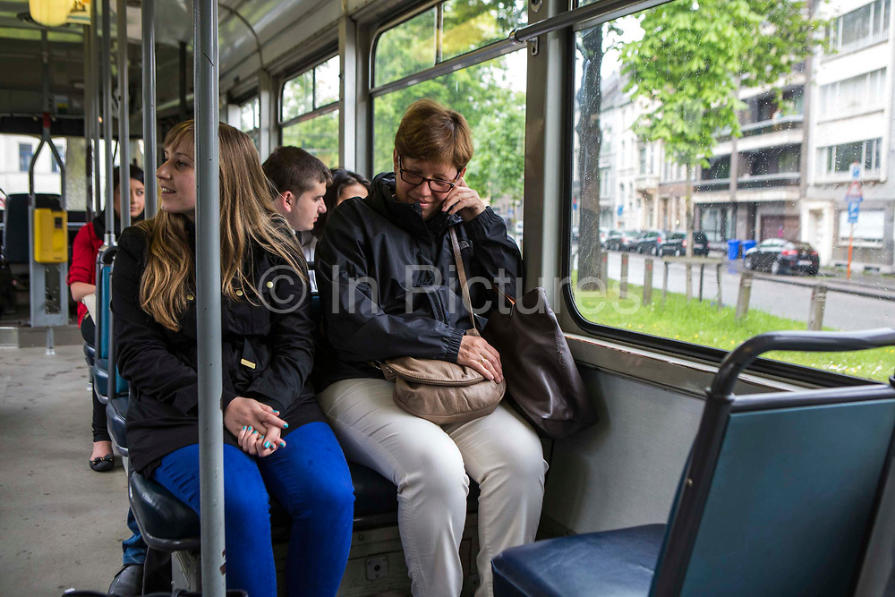 Female passengers sit and travel on an electric tram bus in Ghent, Belgium.