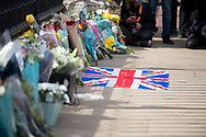 A lone Union Jack flag lays in front of Buckingham Palace alongside flowers In memory of Prince Philip The Royal Highness the Duke of Edinburgh, London on 9 April 2021.