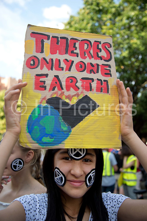 The Air that we Grieve march on July 12th 2019 in East London, United Kingdom. Organised by Extinction Rebellion to draw attention to air pollution and the climate emergency. A young girl has Extinction Rebellion stickers on her face and holds a drawing of the earth.