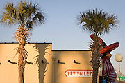 """A fiberglass statue of rest stop mascot """"Pedro"""" stands beside palmettos and restrooms at South of the Border near the North Carolina-South Carolina state line on Interstate 95."""