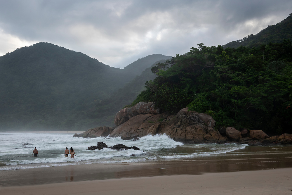 Trinidade, Brazil - March 18, 2019: Late in the afternoon, people stand in the sea at Praia do Meio in Trindade, a small town located near Paraty in Brazil's Rio de Janeiro state.