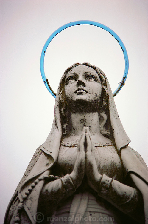 A statue of the Virgin Mary with a blue neon halo in Naples, Italy..
