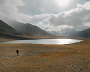 """Lake across Aqbelis. Trekking from a Wakhi pasture called Warm across the wide snowfree Aqbelis Pass, entering the Little Pamir range. Guiding and photographing Paul Salopek while trekking with 2 donkeys across the """"Roof of the World"""", through the Afghan Pamir and Hindukush mountains, into Pakistan and the Karakoram mountains of the Greater Western Himalaya."""