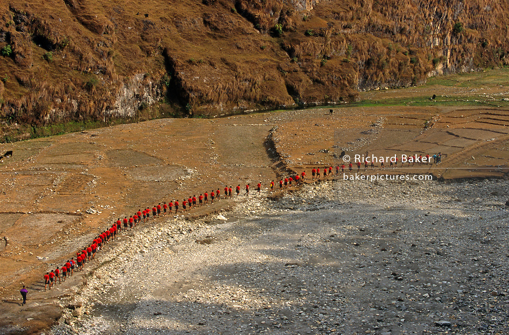 Red identical t-shirts of young Nepali boys walk in single-file through a dry valley near the British Gurkha Regiment's army camp at Pokhara after recently being recruited into the regiment after a gruelling series of tests to eliminate the weaker and less able candidates. 60,000 boys aged between 17-22 (or 25 for those educated enough to become clerks or communications specialists) report to designated recruiting stations in the hills each November, most living from altitudes ranging from 4,000-12,000 feet. After initial selection, 7,000 are accepted for further tests from which 700 are sent down here to Pokhara in the shadow of the Himalayas. Only 160 of the best boys succeed in the journey to the UK. The Gurkhas have been supplying youth for the British army since the Indian Mutiny of 1857.