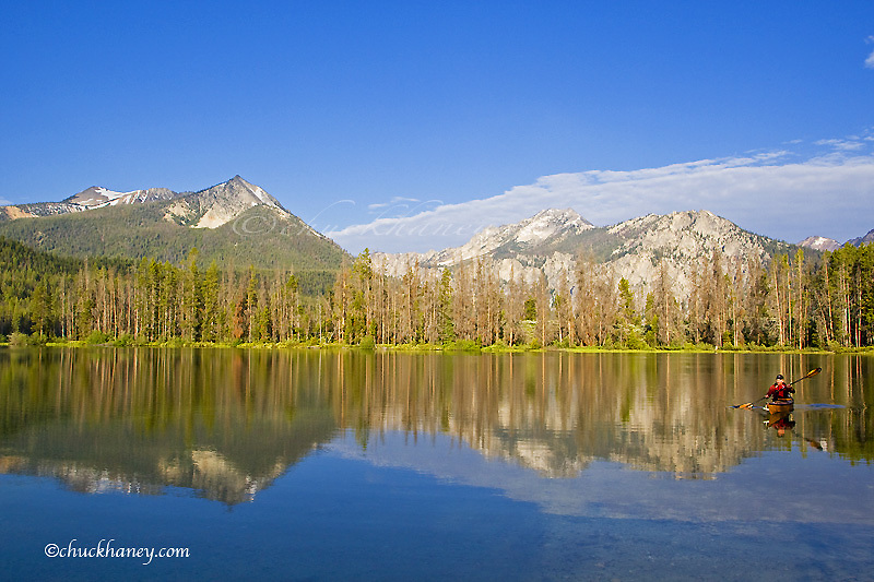 Paddling a sea kayak on a calm Pettit Lake in the Sawtooth Mountains of Idaho model released