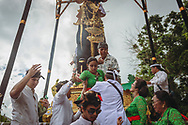 Ubud, Bali, Indonesia - February 13, 2017: A woman is helped off a funeral pyre shortly after it has been set alight at Pura Dalem Puri Peliatan, a temple in Ubud.