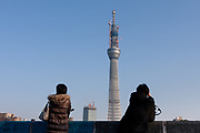 Two Japanese women take in the the view of Tokyo Skytree under construction. Oshiage, Tokyo, Japan. Friday February 4th 2011. When finished this telecommunications tower will measure 634 metres from top to bottom making it the tallest structure in East Asia..