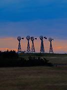 Photograph of windmilss on a ranch in western Nebraska, sunset.
