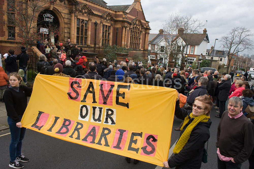 A passionate crowd with a placard blocks the road while demanding Lambeth council keeps their hands of public libraries. Faced with the closure of its beloved local library, the people of Herne Hill, Lambeth, south London hold a demonstration outside the Edwardian library. Lambeth council plan to close the facility used by the community as part of austerity cuts, saying they will convert the building into a gym and privately-owned gentrified businesses - rather than a much-loved reading and learning resource. £12,600 was donated by the American philanthropist Andrew Carnegie to help build the library which opened in 1906. It is a fine example of Edwardian civic architecture, built with red Flettan bricks and terracotta, listed as Grade II in 1981.