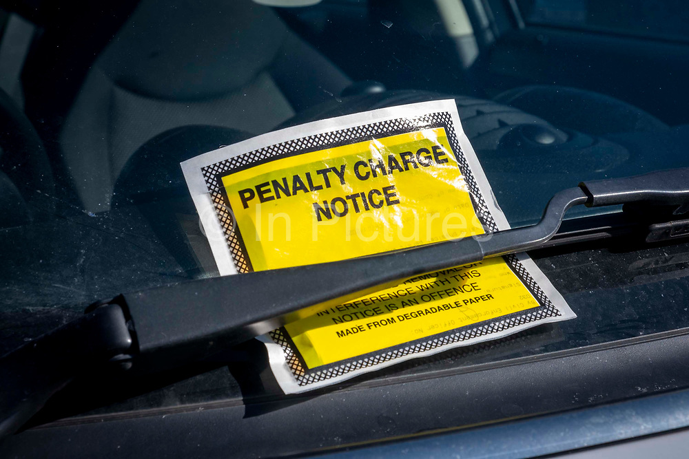 A Penalty Charge notice parking fine placed under the windscreen wiper of a car parked illegally on the 9th of March 2021 in Folkestone, United Kingdom.